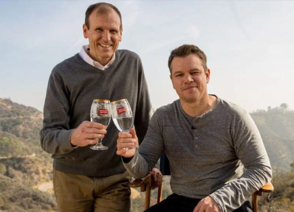 Gary White and Matt Damon holding Stella Artois chalices